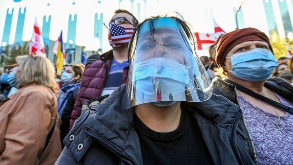 Эпидемия коронавируса - люди в масках на митинге - Sputnik Грузия