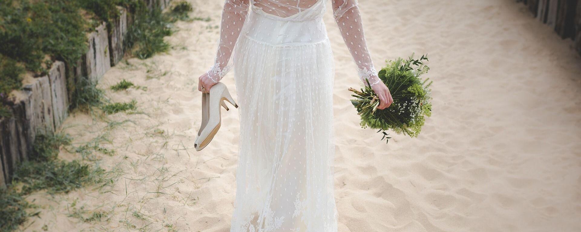 Невеста идет босиком, держа в руках туфли и свадебный букет - Sputnik საქართველო, 1920, 12.03.2021