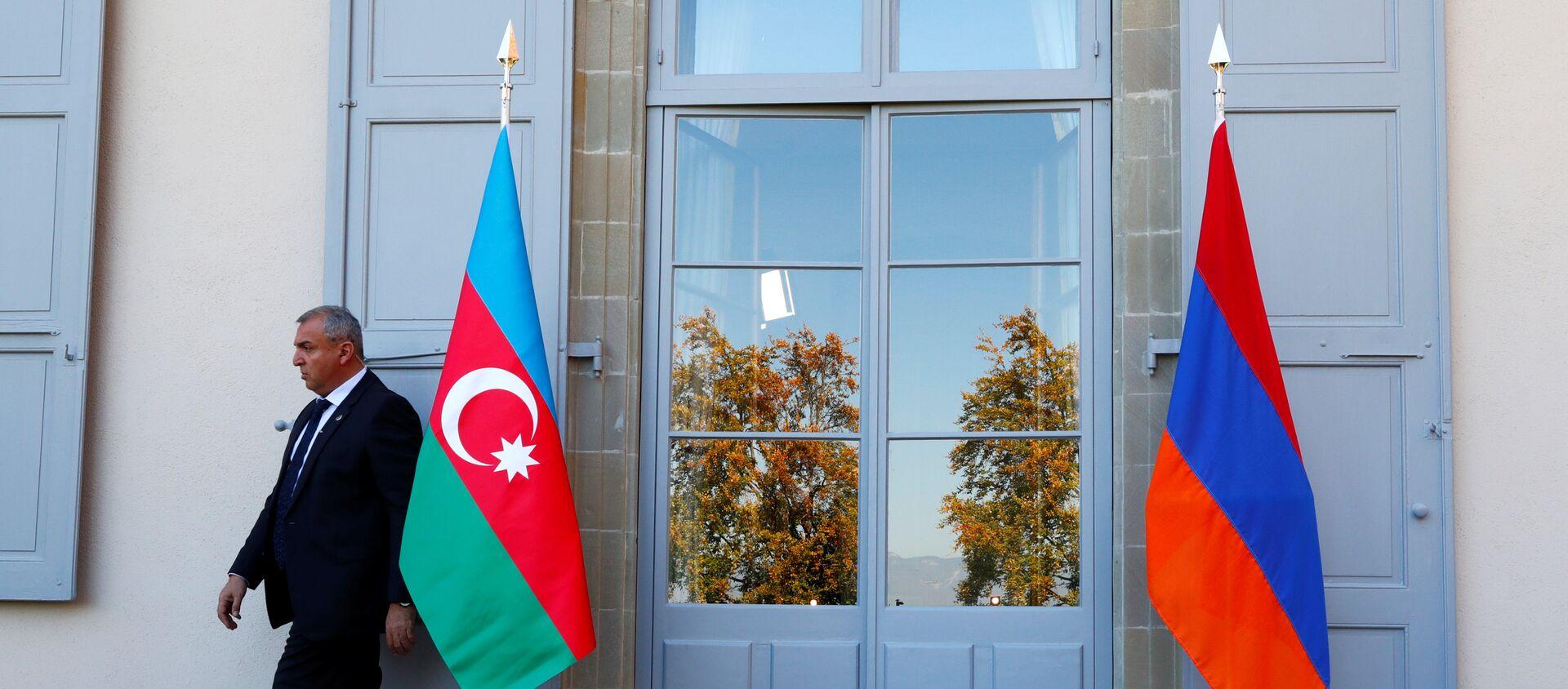 Охранник проходит мимо азербайджанского (слева) и армянского флага на открытии переговоров в Женеве, Швейцария - Sputnik Грузия, 1920, 29.03.2021