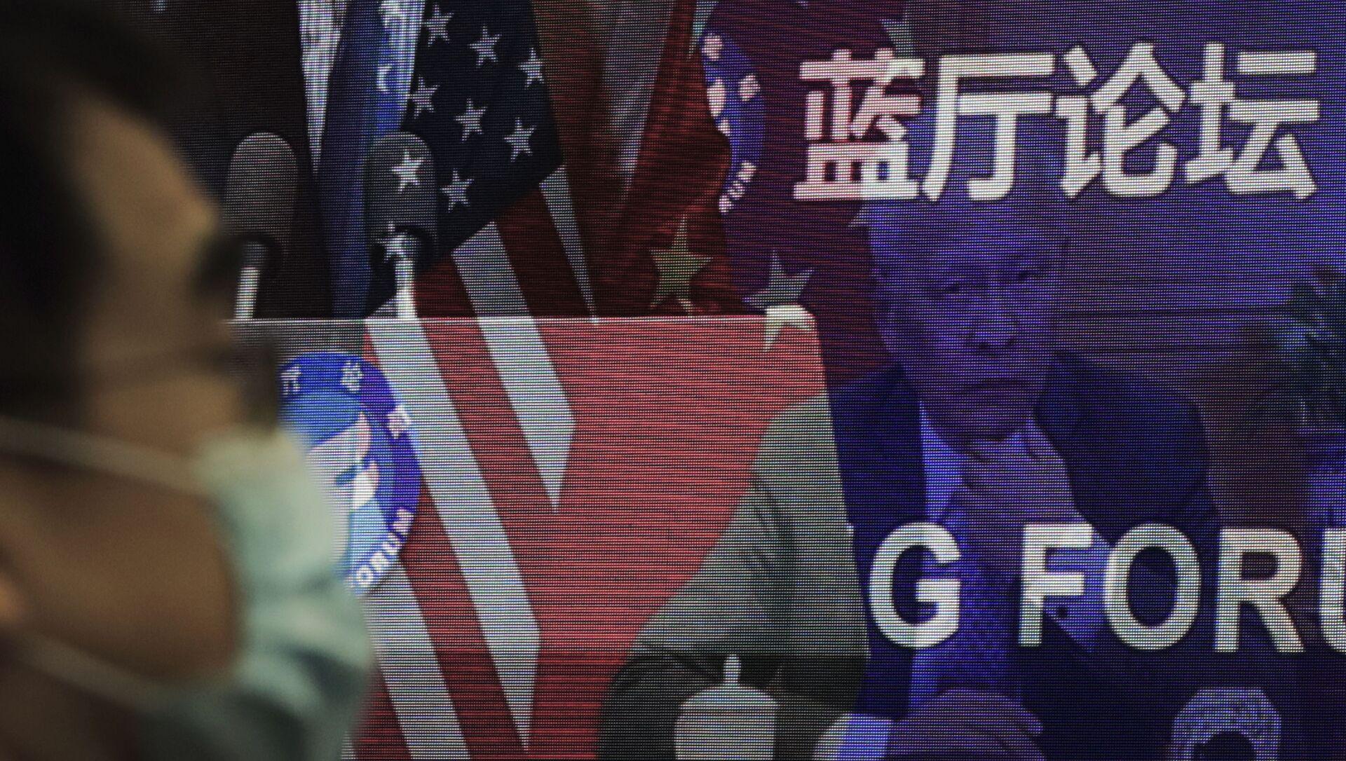 Мужчина в маске, помогающей сдержать распространение коронавируса, сидит возле экрана, демонстрирующего, как делегаты присутствуют на форуме Лантинга, посвященном приезду Китая и США. отношения вернулись в правильное русло, которое под председательством министра иностранных дел Китая Ван И в офисе Министерства иностранных дел в Пекине в понедельник, 22 февраля 2021 года. В понедельник Ван призвал США снять ограничения на торговлю и контакты между людьми при прекращении того, что Пекин считает необоснованным вмешательством в районы Тайваня, Гонконга, Синьцзяна и Тибета - Sputnik Грузия, 1920, 16.04.2021