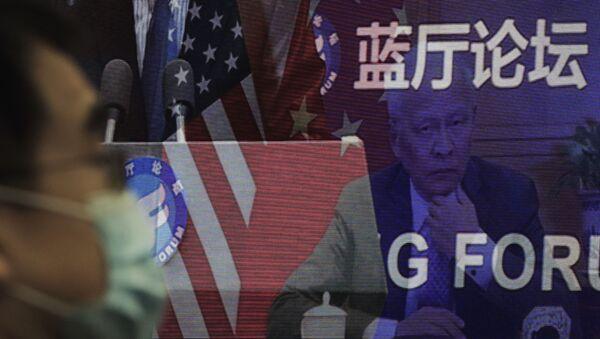 Мужчина в маске, помогающей сдержать распространение коронавируса, сидит возле экрана, демонстрирующего, как делегаты присутствуют на форуме Лантинга, посвященном приезду Китая и США. отношения вернулись в правильное русло, которое под председательством министра иностранных дел Китая Ван И в офисе Министерства иностранных дел в Пекине в понедельник, 22 февраля 2021 года. В понедельник Ван призвал США снять ограничения на торговлю и контакты между людьми при прекращении того, что Пекин считает необоснованным вмешательством в районы Тайваня, Гонконга, Синьцзяна и Тибета - Sputnik Грузия