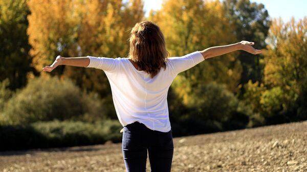 Женщина с раскинутыми руками в лесу радуется солнцу и теплу - Sputnik Грузия