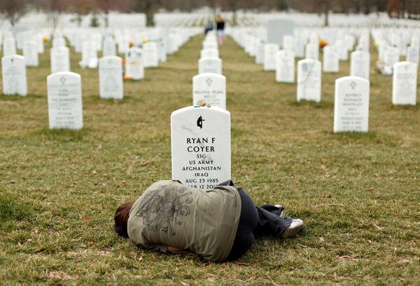 Житель штата Мичиган Лесли Койер лежит у могилы своего брата Райана Койера, служившего в армии США в Ираке и Афганистане. Арлингтонское национальное кладбище в Вирджинии, 11 марта 2013 года - Sputnik Грузия