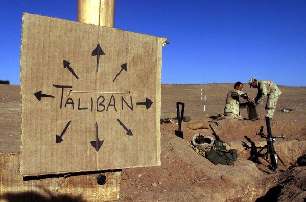 Морские пехотинцы США размещают мешки с песком вокруг позиции из легких минометов на передовой. Рядом висит табличка, напоминающая всем, что силы Талибана могут быть где угодно. Юг Афганистана, 1 декабря 2001 года - Sputnik Грузия