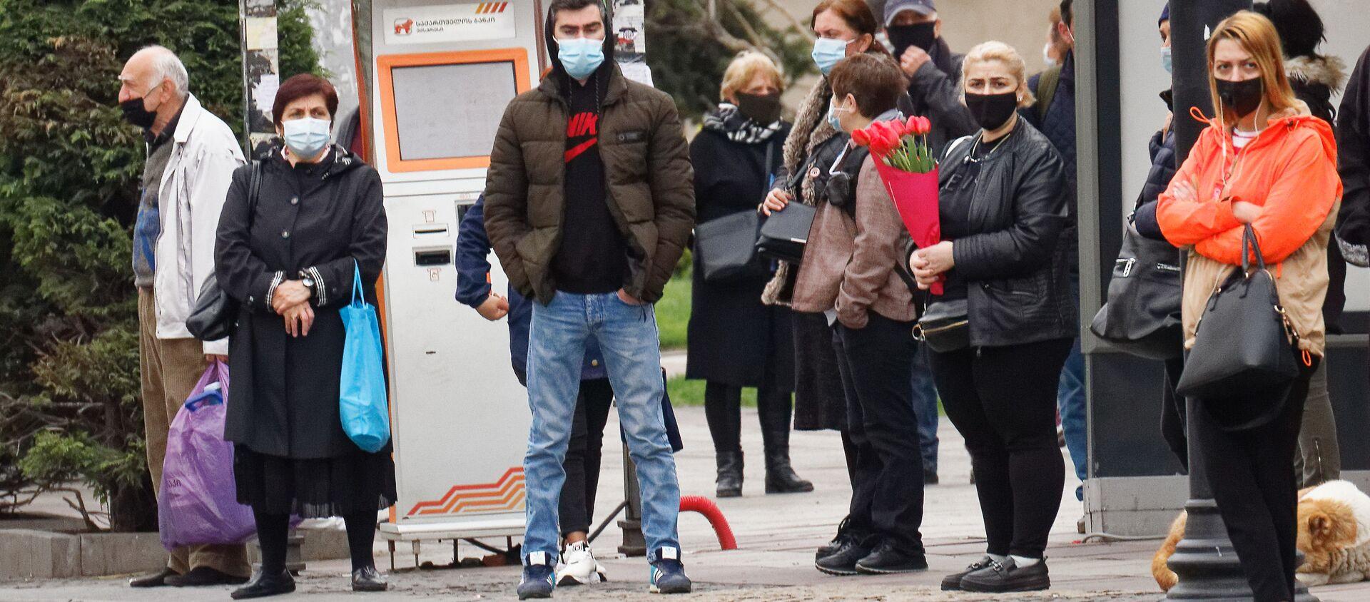 Эпидемия коронавируса - прохожие на автобусной остановке в масках - Sputnik Грузия, 1920, 28.04.2021