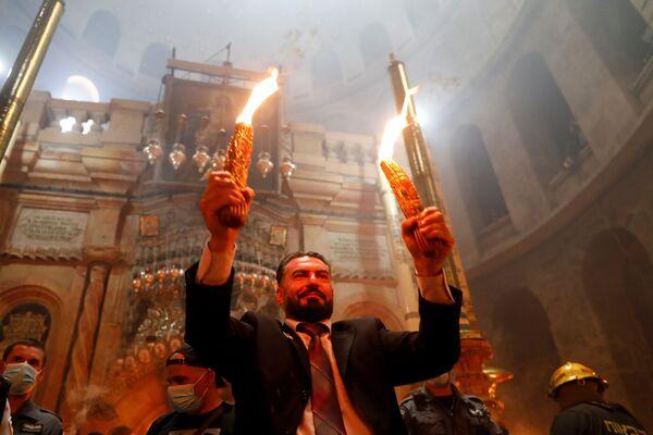После того, как огонь появился в эту субботу,патриарх Иерусалимский Феофил III раздал его служителям Греческой церкви и представителям других конфессий, владеющих храмом Гроба Господня - Sputnik Грузия