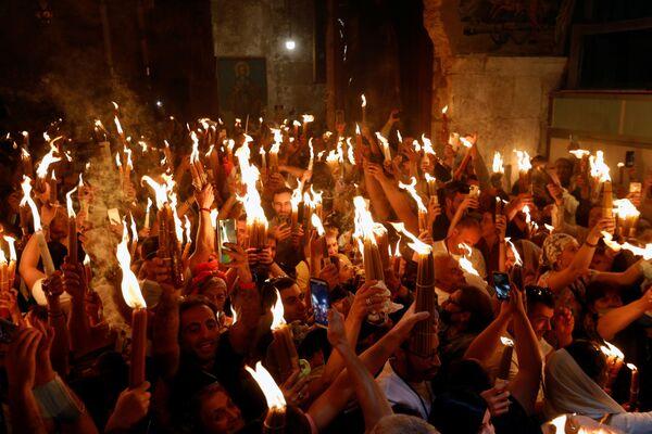 Его появление в канун православной Пасхи по молитвам православного патриарха, духовенства и тысяч паломников, несмотря на регулярность, называют чудом схождения Благодатного огня - Sputnik Грузия