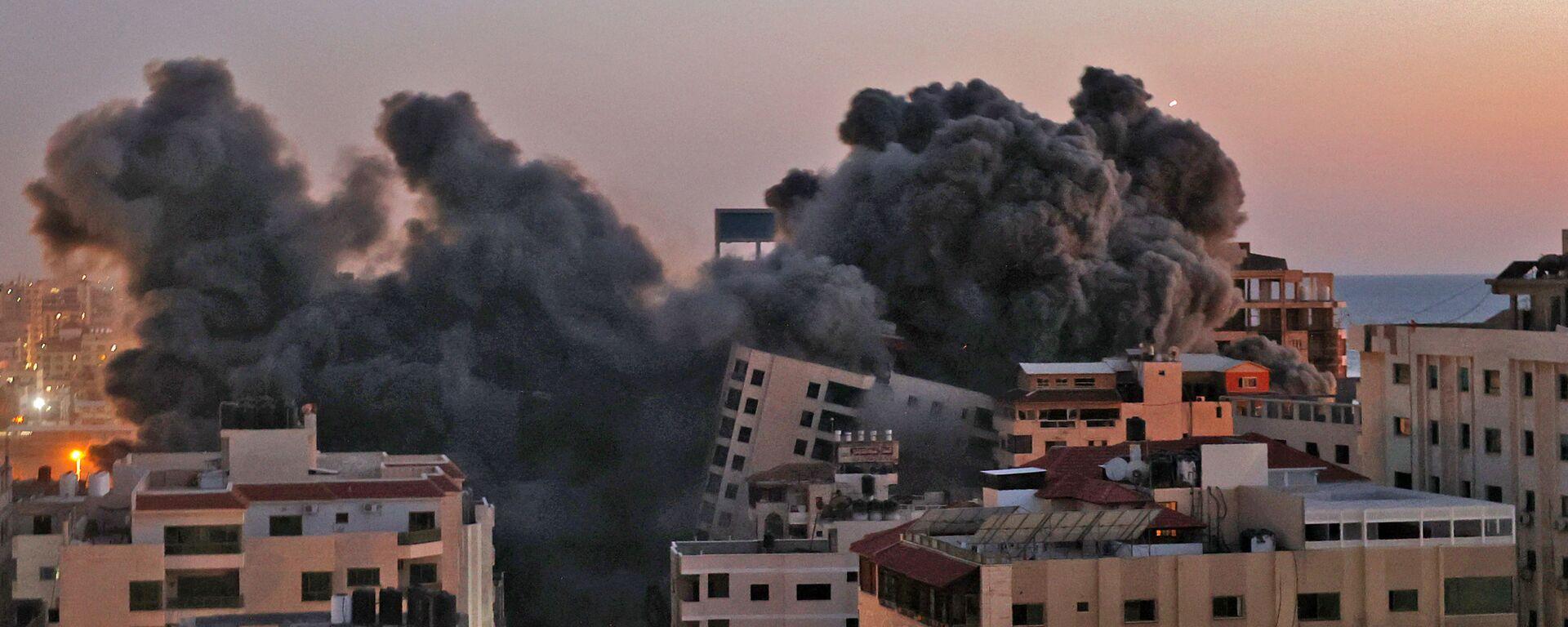 Пожарные тушат горящие многоквартирные дома после израильских авиаударов в городе Газа - Sputnik Грузия, 1920, 12.05.2021
