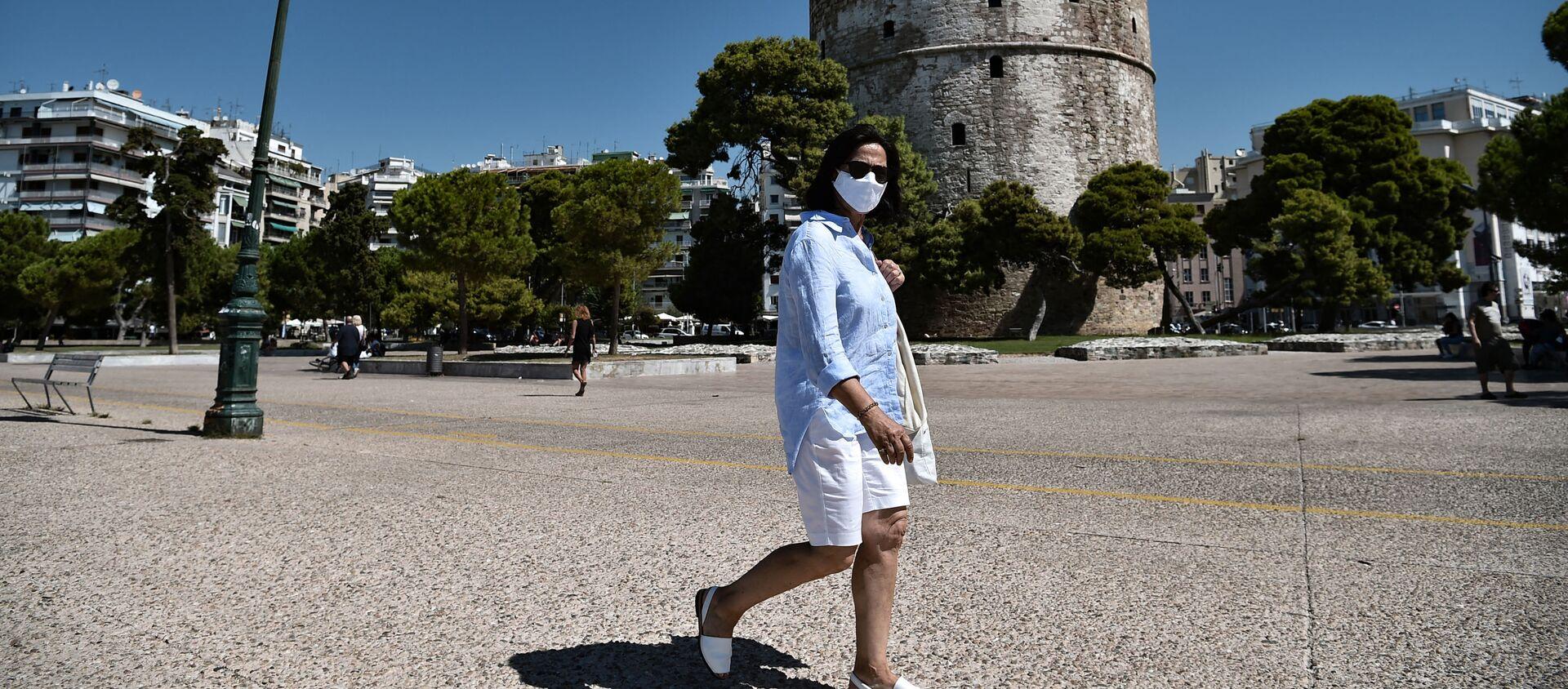 Женщина в защитной маске прогуливается рядом с Белой башней в Салониках  - Sputnik Грузия, 1920, 14.05.2021