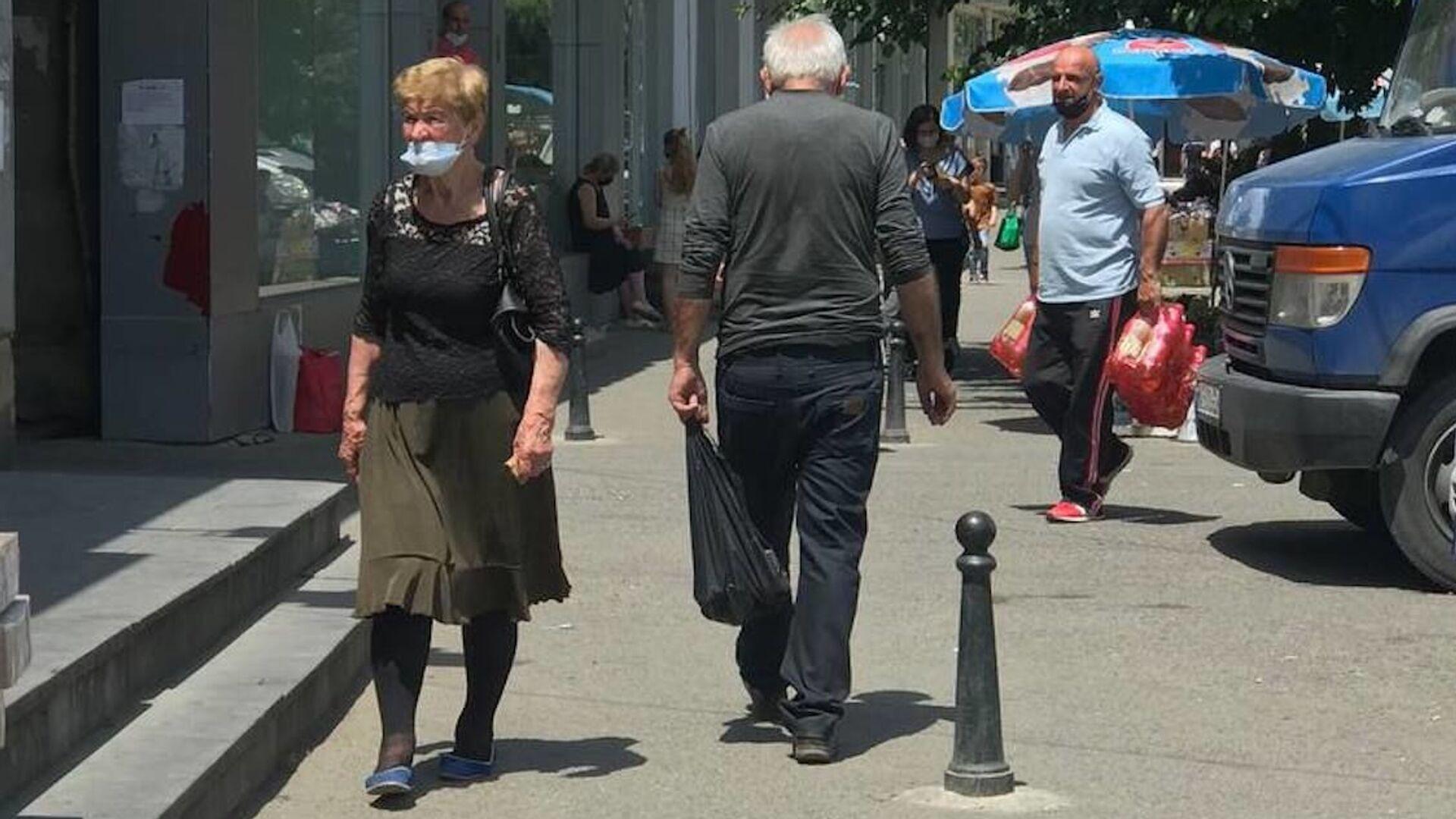 Эпидемия коронавируса. Прохожие на улицах города в масках - Sputnik Грузия, 1920, 12.09.2021