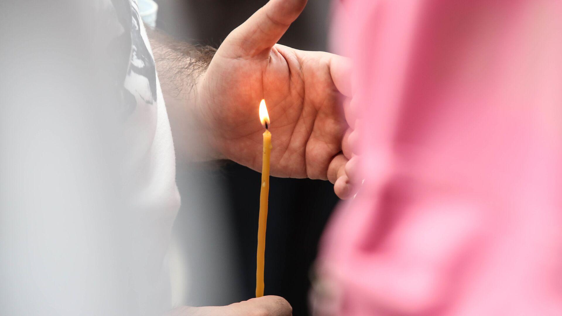 Верующие держат в руках горящие свечи во время молитвы - Sputnik Грузия, 1920, 12.10.2021