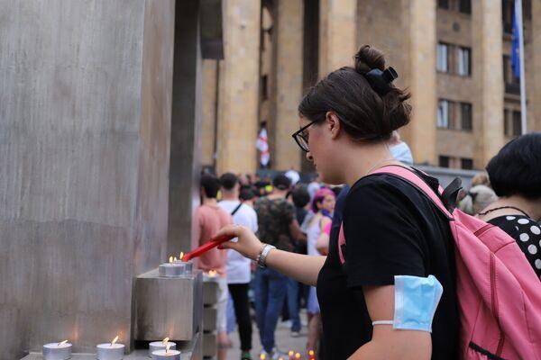 У здания парламента Грузии параллельно с митингом также проходила траурная акция - люди приносили цветы и зажигали свечи в память о погибшем телеоператоре Лексо Лашкарава - Sputnik Грузия