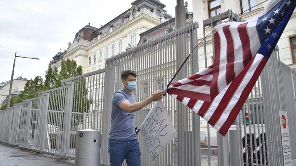 Протестующий сторонник BLM в Вене, Австрия, с флагом США у посольства Соединенных Штатов - Sputnik Грузия