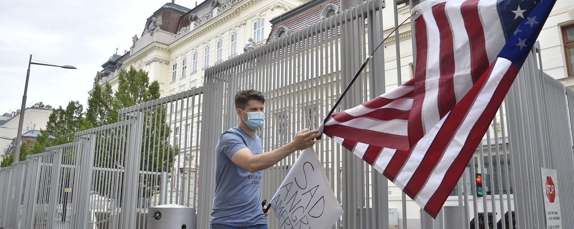 Протестующий сторонник BLM в Вене, Австрия, с флагом США у посольства Соединенных Штатов - Sputnik Грузия, 1920, 21.07.2021