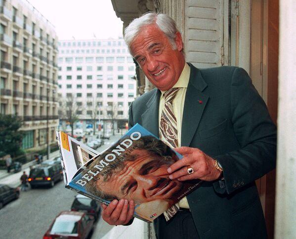 Кинокарьеру Бельмондо называют одной из самых коммерчески успешных во Франции. На фото: Бельмондо с книгой о себе - Sputnik Грузия