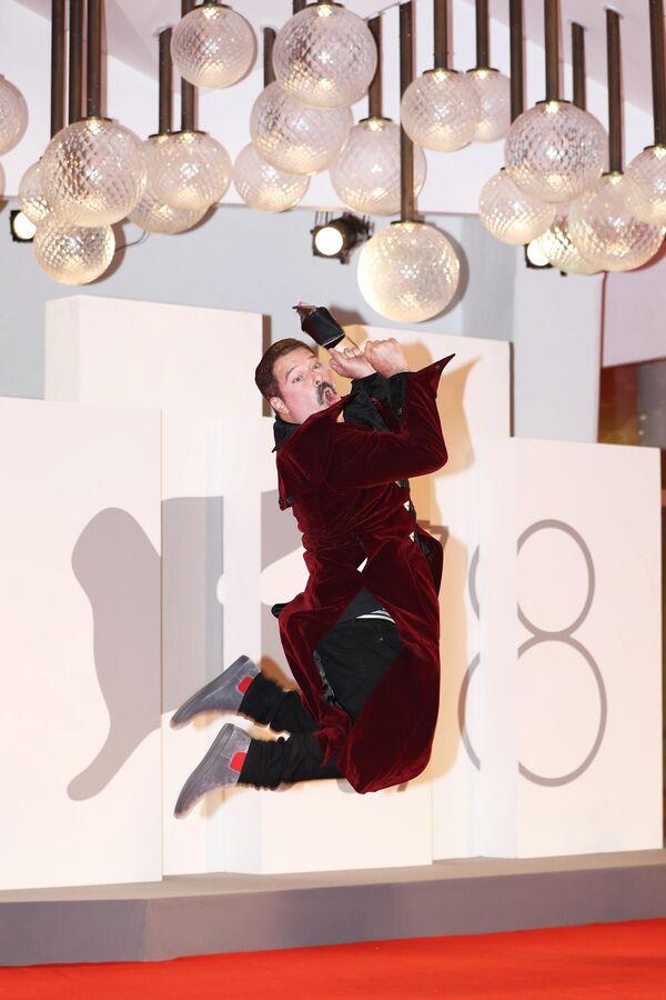 """Актер Джоэль Майкли на красной дорожке премьеры фильма режиссера Пола Шредера """"Холодный расчет""""  позирует на камеру в прыжке и с маской в руке - Sputnik Грузия"""