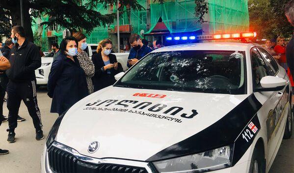 Местные жители ждут новостей у полицейской машины. Один из очевидцев сообщил, что преступник вооружен гранатой - Sputnik Грузия