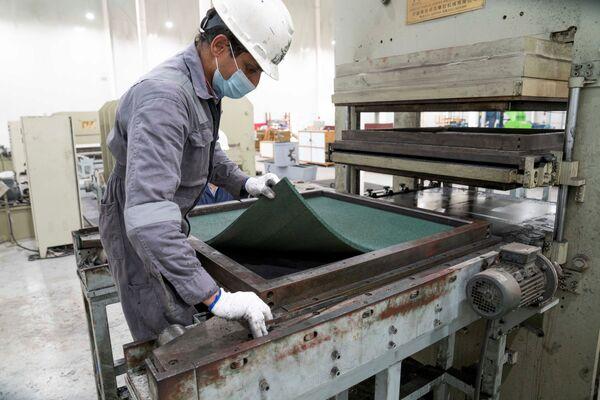 Сотрудники перерабатывающего завода сортируют и измельчают старые шины, чтобы затем изготовить коврики для пола - Sputnik Грузия