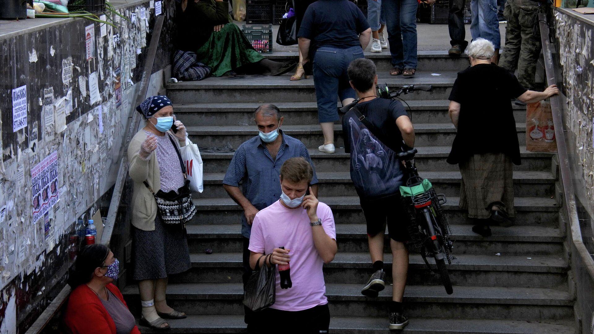 Эпидемия коронавируса - прохожие в масках в подъемном переходе - Sputnik Грузия, 1920, 16.09.2021