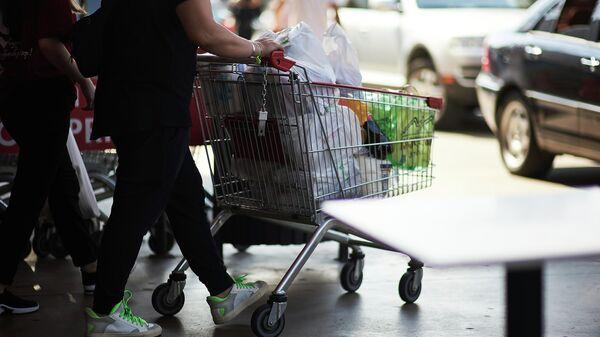 Покупатели в супермаркете - мужчина выкатывает тележку с продуктами - Sputnik Грузия