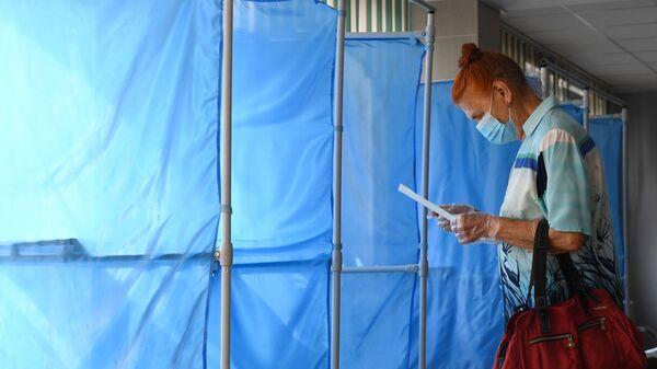 Женщина принимает участие в голосовании по внесению поправок в Конституцию РФ на избирательном участке №1503 в Новосибирске - Sputnik Грузия