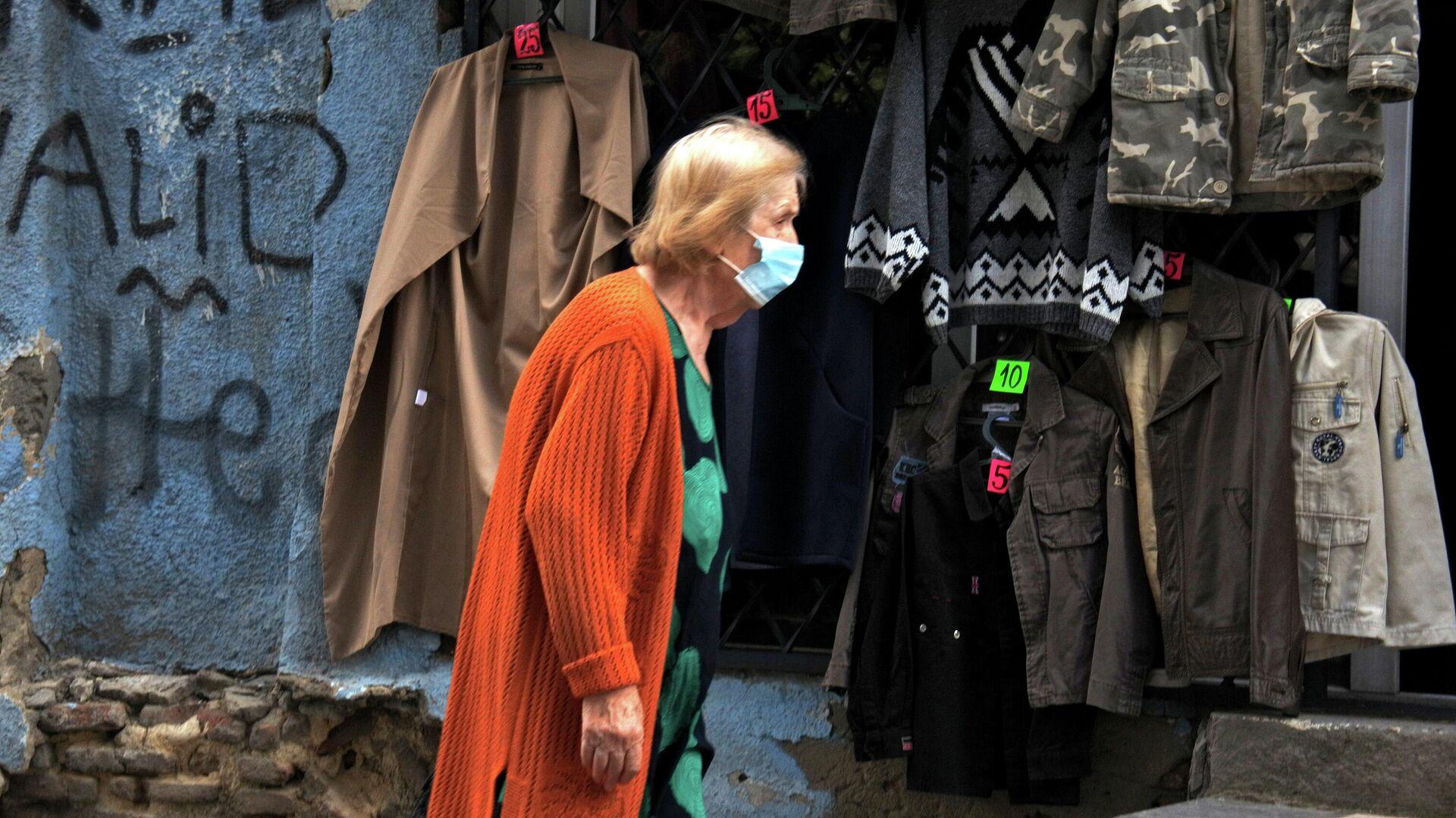 Эпидемия коронавируса - пожилая женщина идет мимо магазина одежды секонд-хенд - Sputnik Грузия, 1920, 23.09.2021