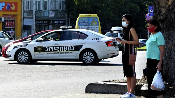 Эпидемия коронавируса - прохожие на улице в масках и патрульная полиция - Sputnik Грузия