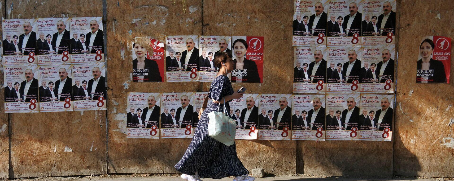 Предвыборная реклама - прохожие идут вдоль забора с плакатами партии Альянс патриотов Грузии - Sputnik Грузия, 1920, 28.09.2021