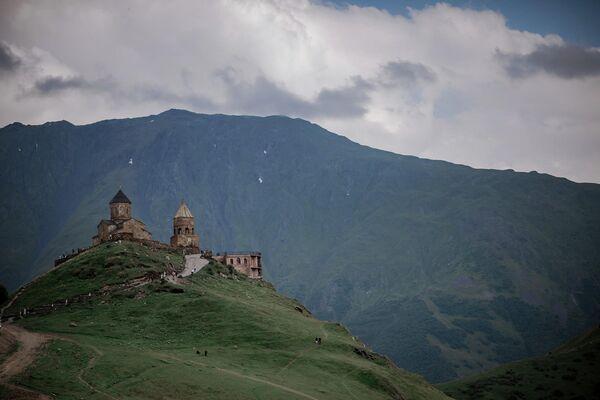 Такой вид на Степанцминда открывается с территории Троицкой церкви XIV века в Гергети. Она тоже окружена горными вершинами.  - Sputnik Грузия