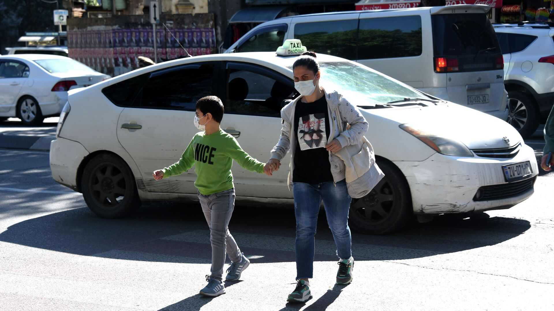 Эпидемия коронавируса - прохожие на улице в масках рядом с такси - Sputnik Грузия, 1920, 08.10.2021