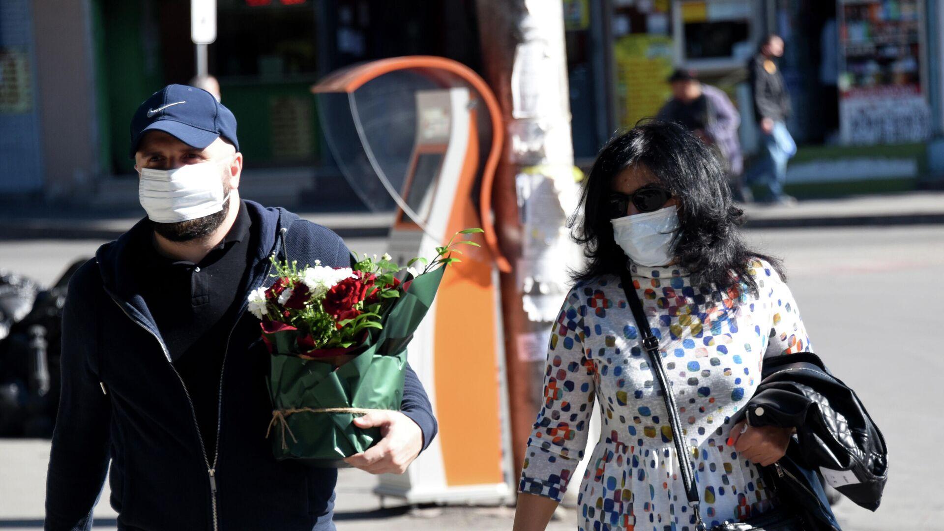 Эпидемия коронавируса - прохожие на улице города в масках, мужчина несет цветы - Sputnik Грузия, 1920, 14.10.2021