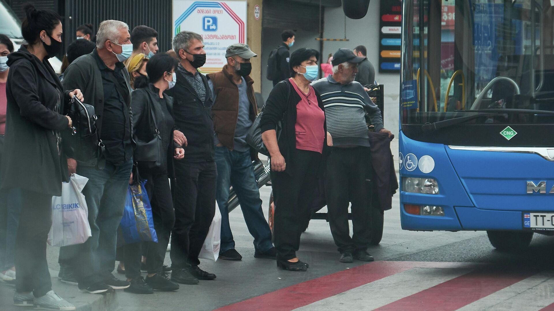 Эпидемия коронавируса - пассажиры на автобусной остановке в масках - Sputnik Грузия, 1920, 30.09.2021