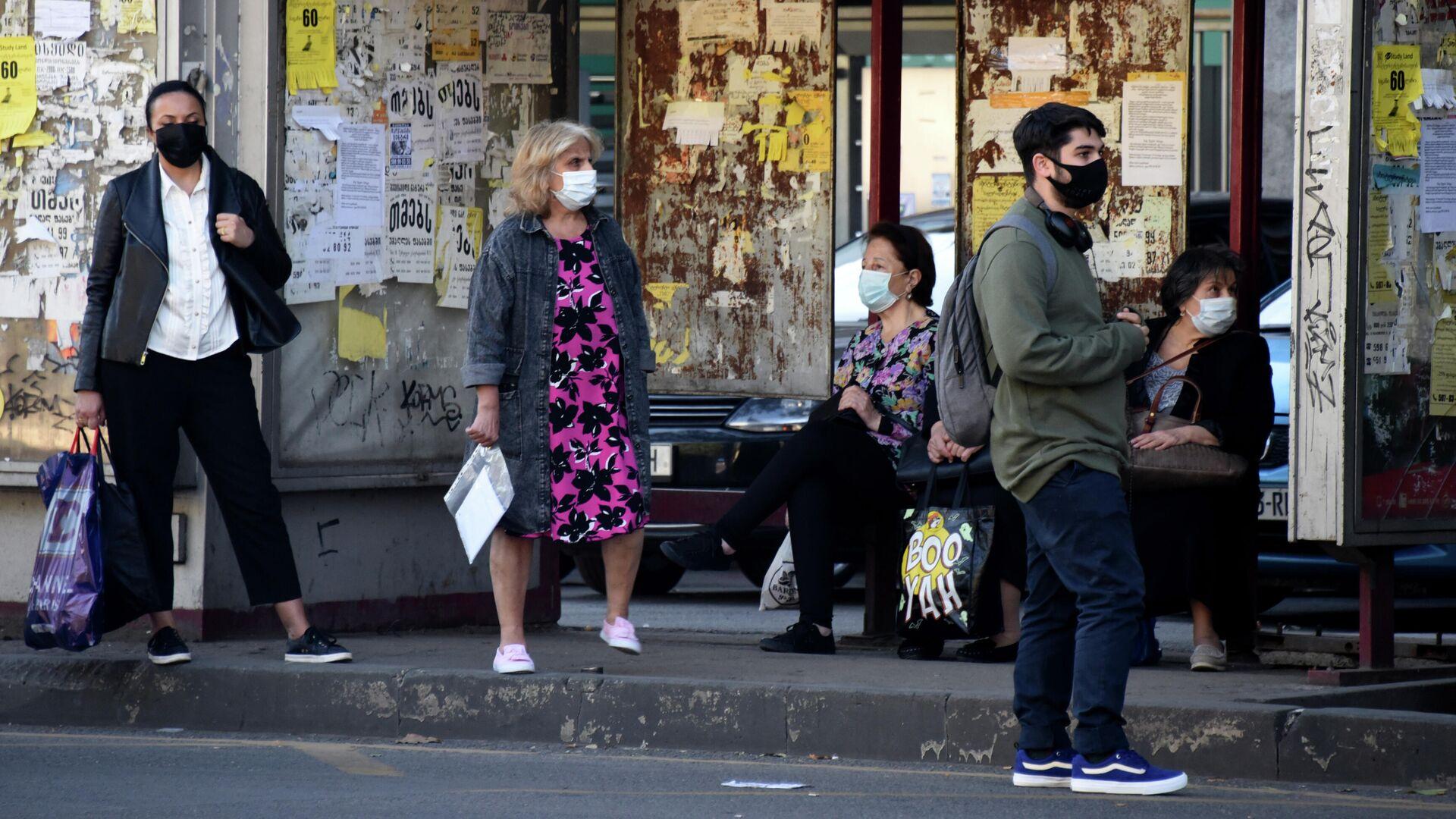 Эпидемия коронавируса - прохожие на улице в масках на автобусной остановке - Sputnik Грузия, 1920, 01.10.2021