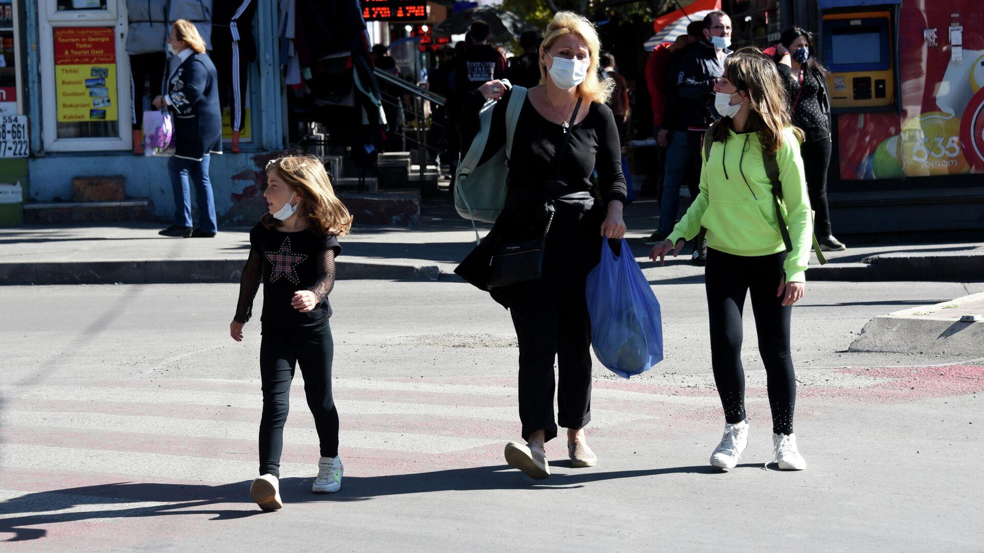 Эпидемия коронавируса - прохожие на улице в масках. Женщина с детьми переходит дорогу - Sputnik Грузия, 1920, 07.10.2021