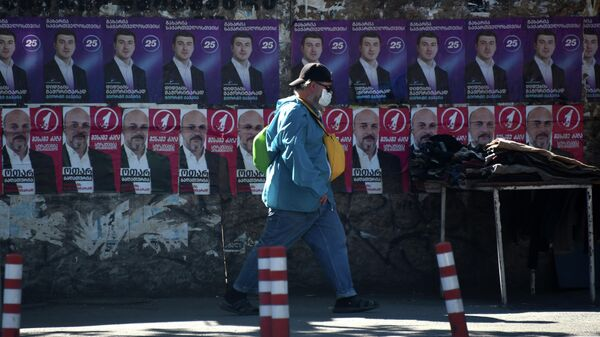 Эпидемия коронавируса и местные выборы - мужчина в маске идет мимо предвыборных плакатов - Sputnik Грузия