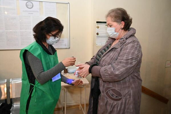 Из-за пандемии коронавируса маски стали уже обязательным антрибутом как для избирателей, так и сотрудников избирательных администраций - Sputnik Грузия