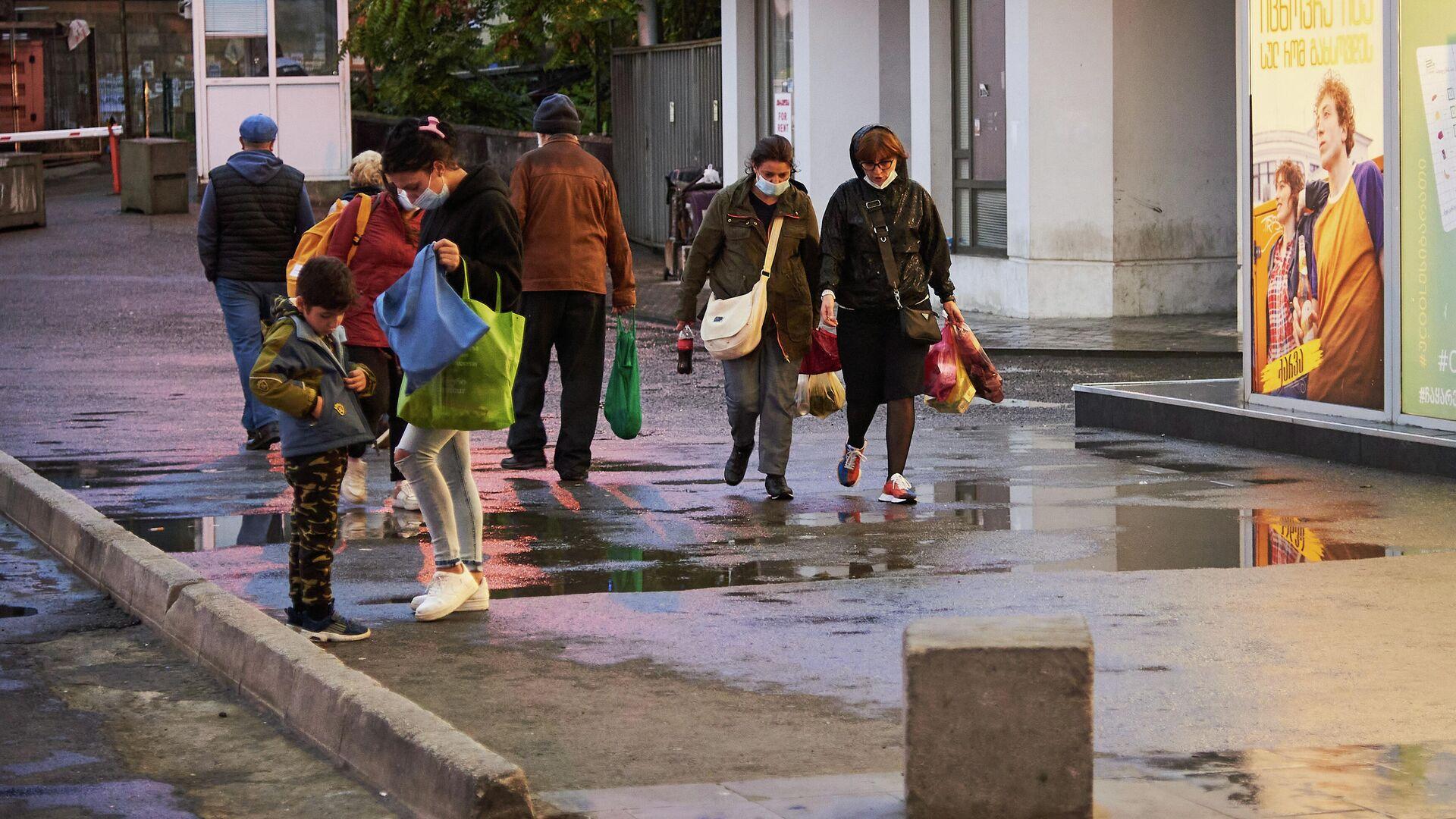 Эпидемия коронавируса - прохожие на улице в масках с покупками, Вокзальная площадь - Sputnik Грузия, 1920, 03.10.2021