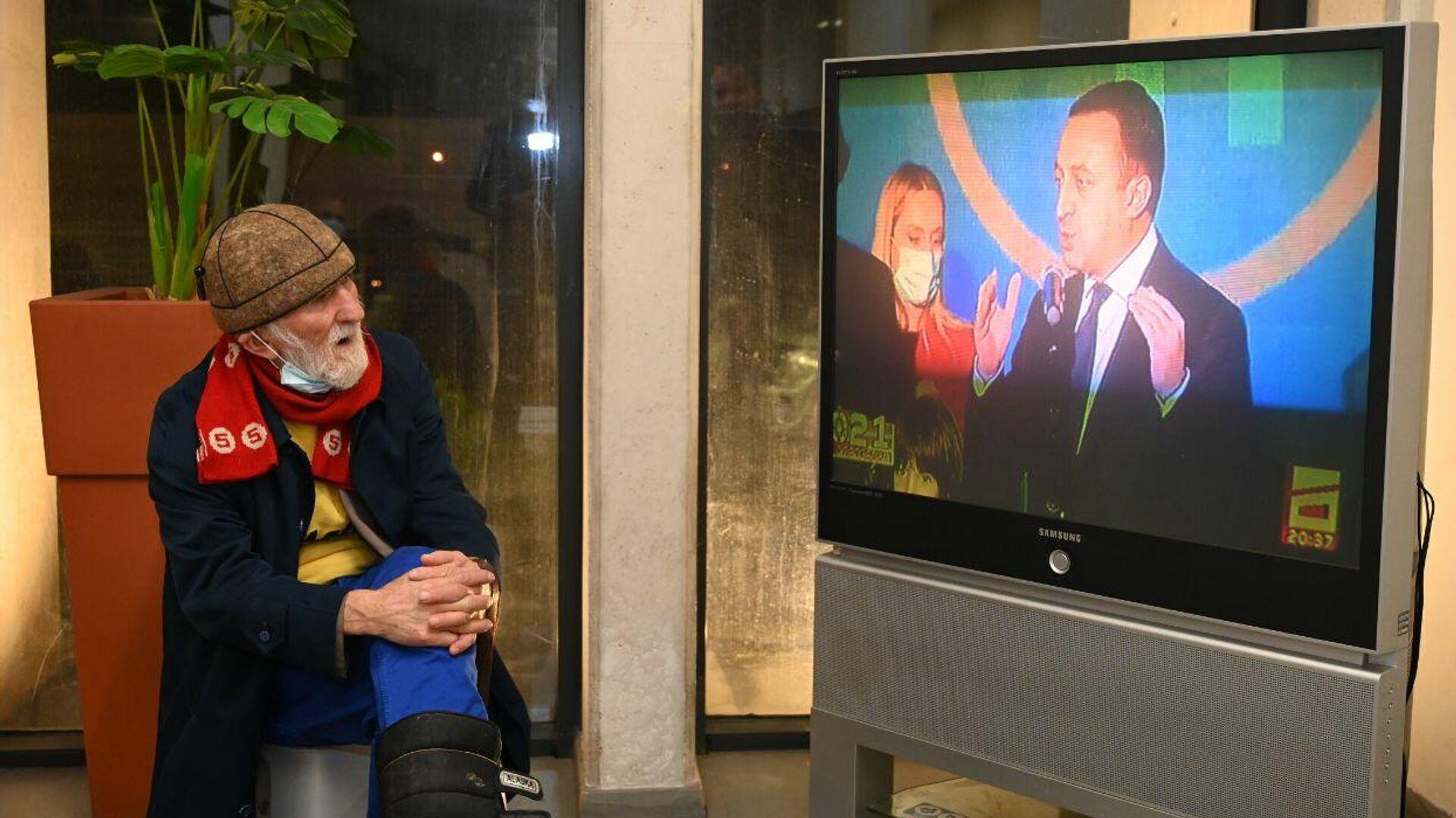 Дедушка в офисе ЕНД смотрит выступление Ираклия Гарибашвили после выборов - Sputnik Грузия, 1920, 03.10.2021