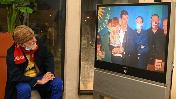 Дедушка в офисе ЕНД смотрит выступление Каладзе и лидеров Грузинской мечты после выборов - Sputnik Грузия