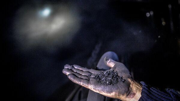 Шахтер показывает уголь на шахте - Sputnik Грузия