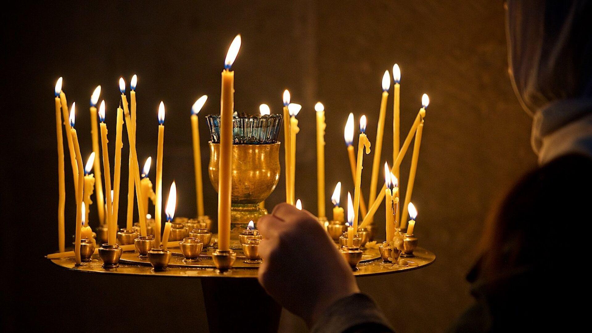 Верующая ставит свечу у иконы в кафедральном соборе Светицховели - Sputnik Грузия, 1920, 13.09.2021