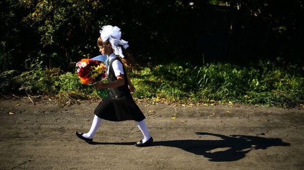 Девочка идёт в школу на торжественную линейку, посвященную Дню знаний, в село Новолуговое Новосибирской области - Sputnik Грузия
