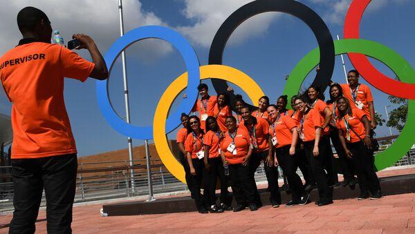 Волонтеры фотографируются у олимпийских колец в Олимпийском парке в Рио-де-Жанейро - Sputnik Грузия