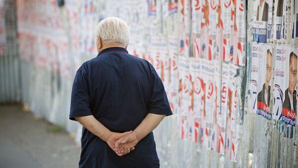 Мужчина проходит мимо предвыборных плакатов - Sputnik Грузия