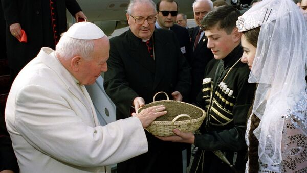 Девочка и мальчик, одетые в традиционные одежды, преподнесли на блюде Иоанну Павлу II грузинскую землю для поклонения. Из-за плохого самочувствия понтифик не смог склониться к ней сам, как это делал по традиции. - Sputnik Грузия