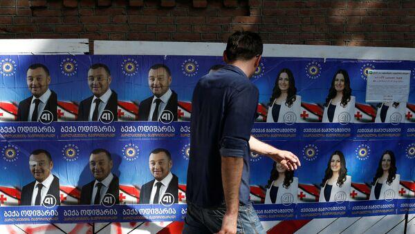 Человек проходит мимо предвыборных плакатов - Sputnik Грузия