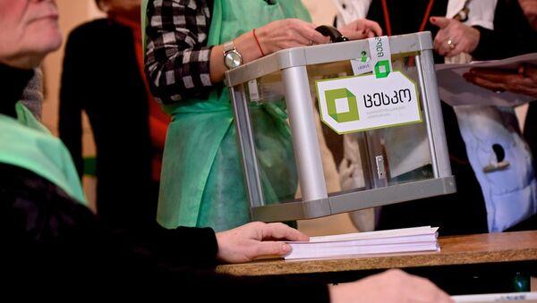 Сотрудники избирательной администрации выносят с участка переносную урну для голосования - Sputnik Грузия