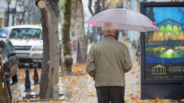 Прохожий идет дождливым утром по грузинской столице - Sputnik Грузия