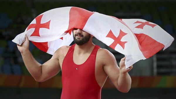 Борец Гено Петриашвили держит флаг Грузии, празднуя победу - Sputnik Грузия
