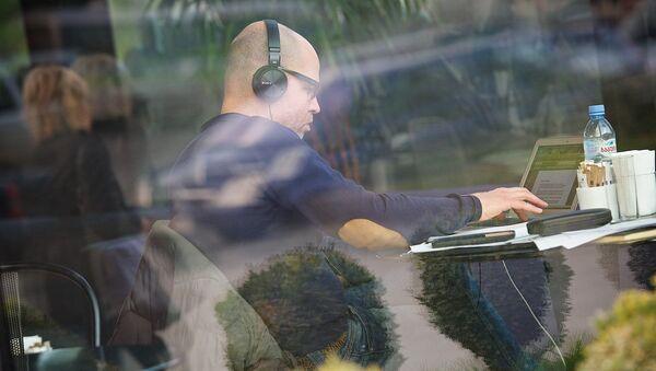 Мужчина работает на ноутбуке сидя за столиком кафе грузинской столицы - Sputnik Грузия